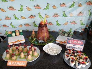 Dinosaur Party Dessert Table with Volcano Cake, Dino Cake Pops, Mini Candy Volcanoes, Dirt Pudding, and Dino Bones