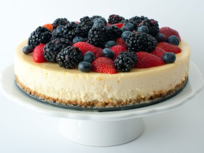 """9"""" round cheesecakes with berries on top."""